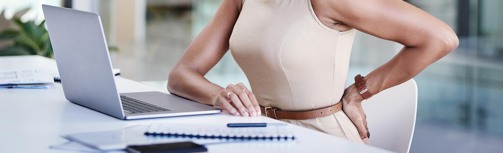 image_of_woman_at_desk_wincing_in_pain_touching_lower_back_GettyImages-1140355942_1800