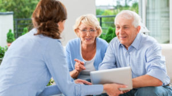 Cheerful senior couple having meeting with financial advisor or insurance agent at home