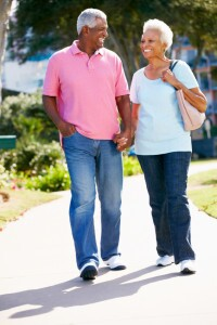 Senior African-American Couple Walking In Park Together