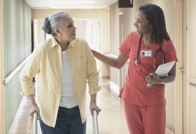 Older patient talking with nurse in hospital