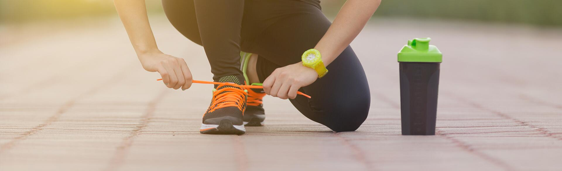 woman tying her shoe while exercising