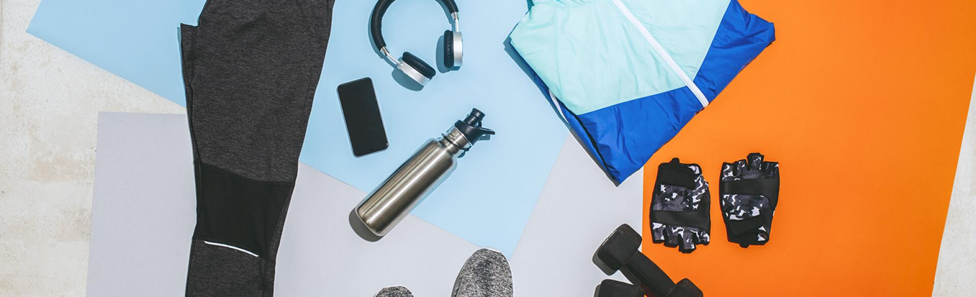 A photo of fitness gear, including sneakers, a workout outfit, a jumprope, and free weights.