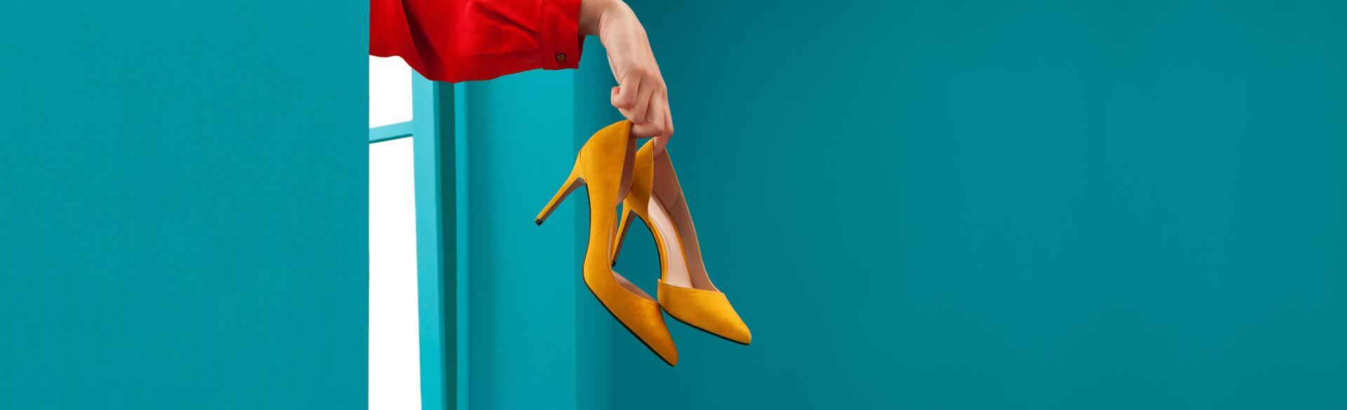 Woman throwing yellow high heels out a window