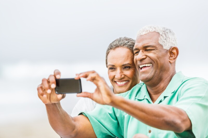 Senior African American couple having fun with smartphone on bea