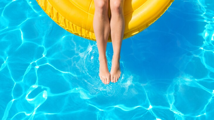 Woman floating on inflatable tube in pool on vacation in summer