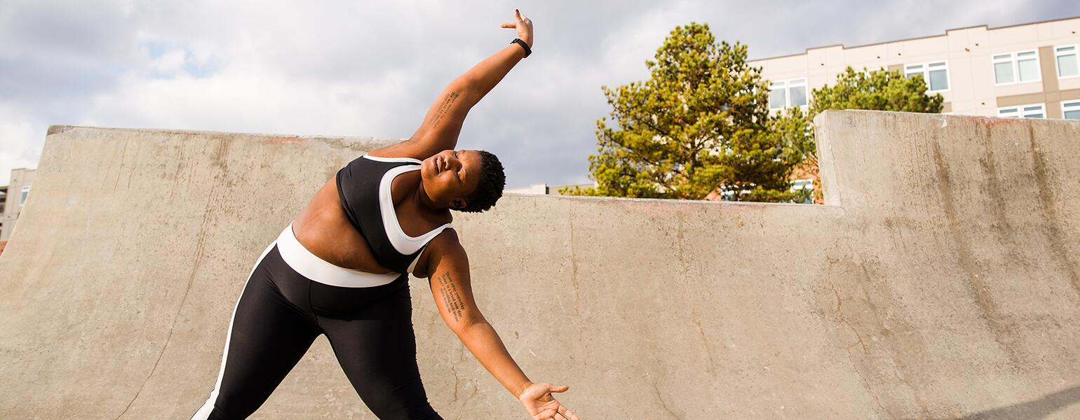 A woman stands on a ramp posing for an Instagram photo, stretching to her left side.