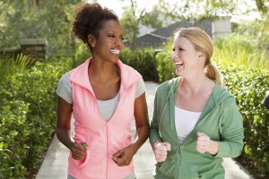 Two women jogging outside on a sunny day