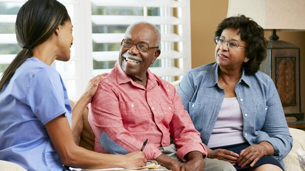 older couple talk to a nurse in their home