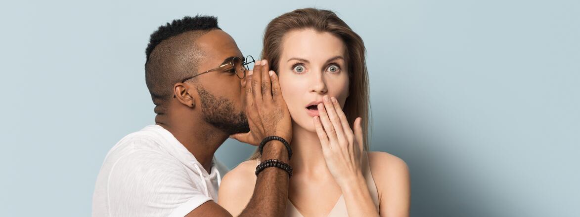 African American man tell secret to shocked caucasian female