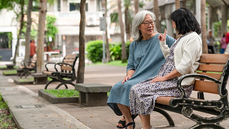 Two women sitting and talking with each other on a park bench