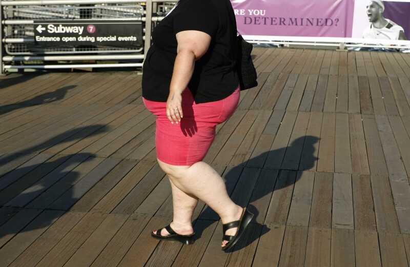 An obese woman walks on the boardwalk