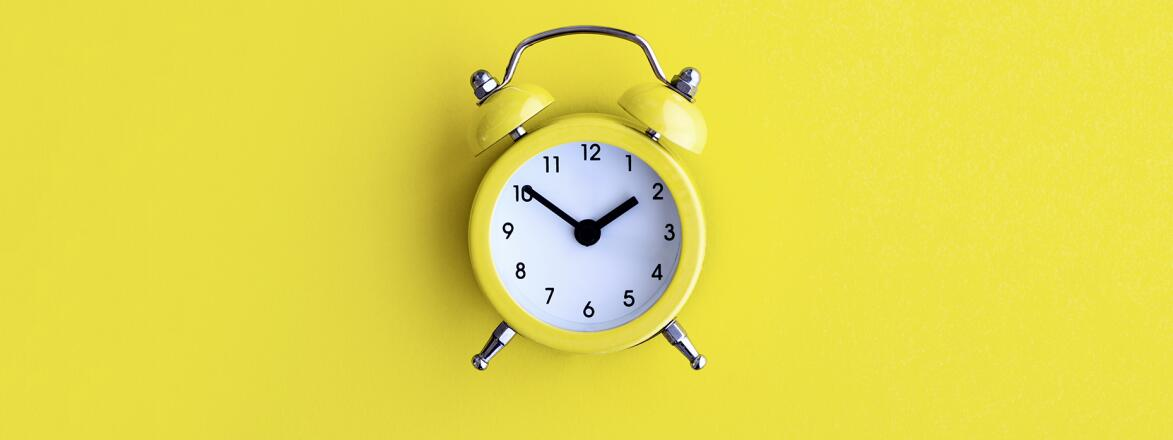 yellow alarm clock on a yellow background