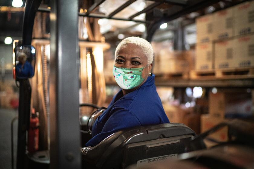 woman_wearing_mask_working_in_warehouse_GettyImages-1264076516