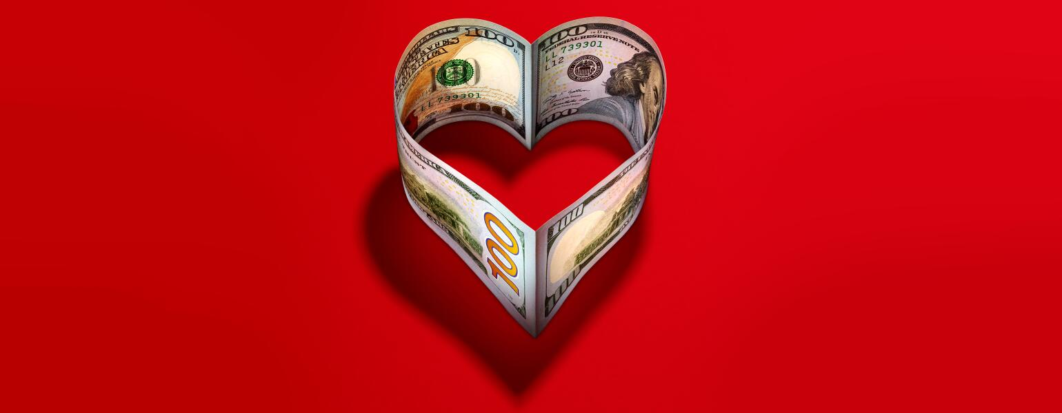 heart made of 100 dollar bills on a red background