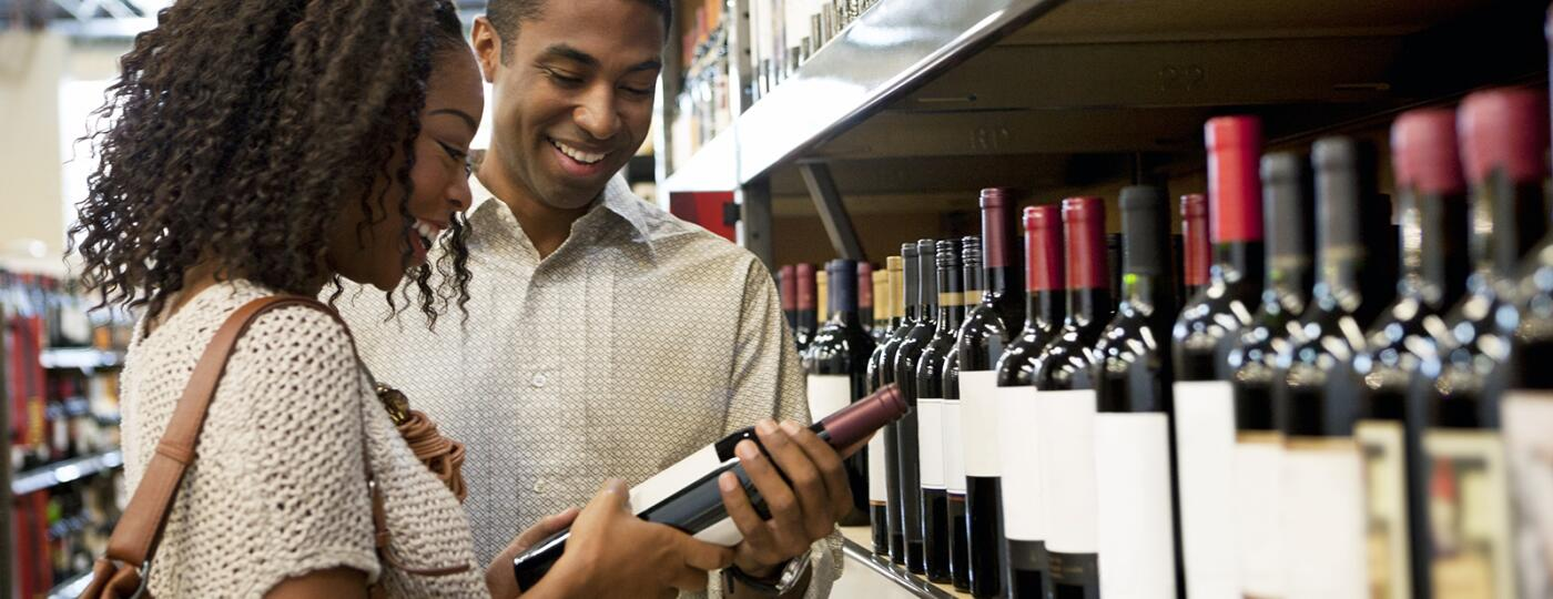 image_of_couple_looking_at_wine_in_wine_shop_GettyImages-143070333_1800