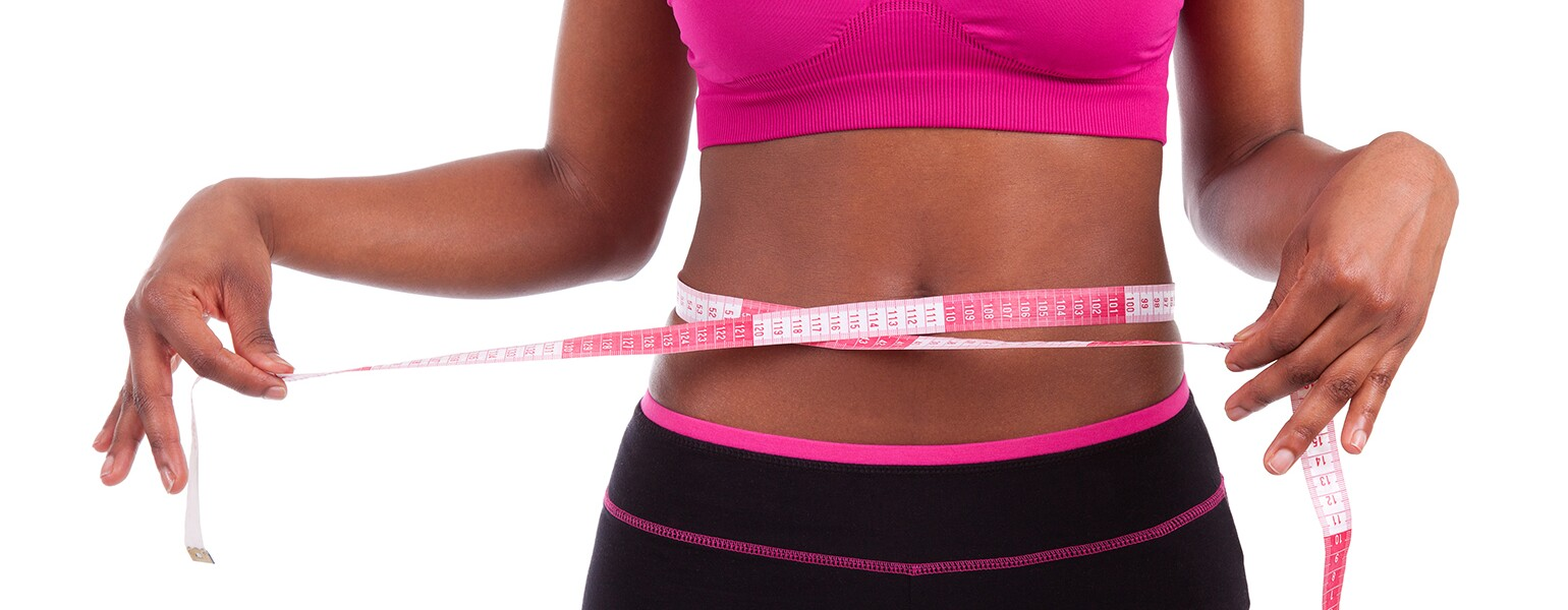 African American athlete with tape measure around stomach