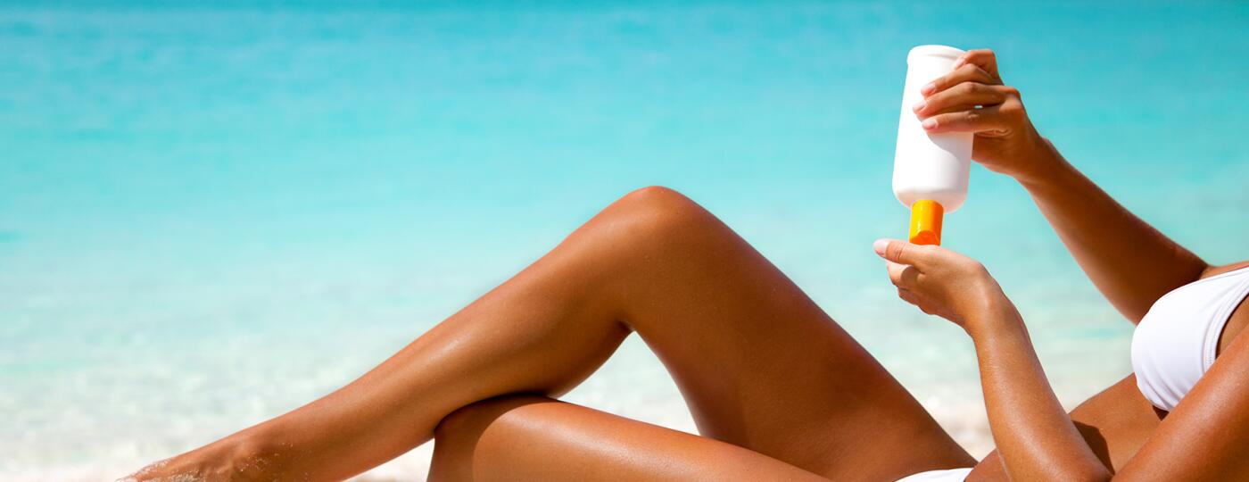 image_of_womans_legs_on_beach_with_sunscreen_lotion_GettyImages-175404710_1800