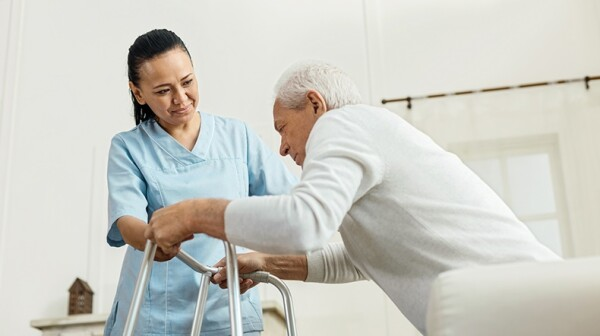 Nurse helping older man with a walker