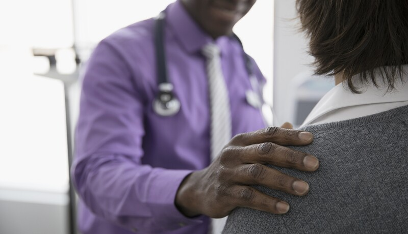 Caring male doctor touching shoulder of female patient in examination room