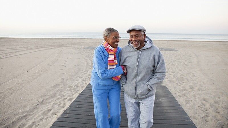 A man and woman smiling and walking together on the beach
