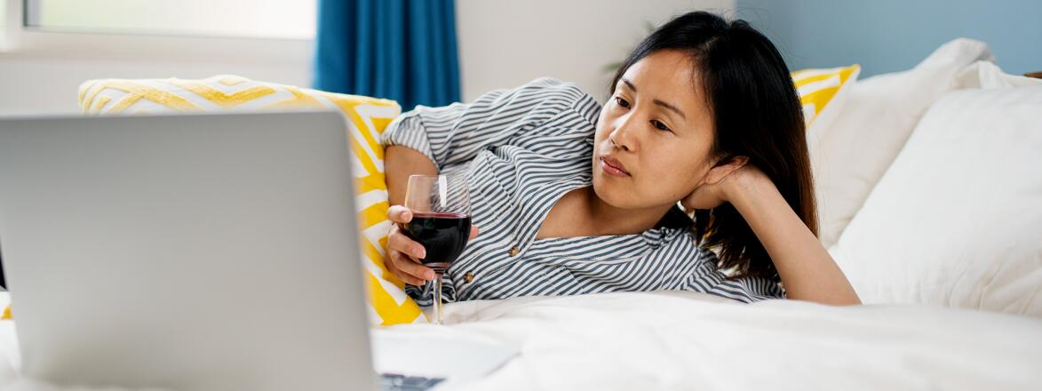 woman watching tv on her computer while laying on her bed with a glass of red wine