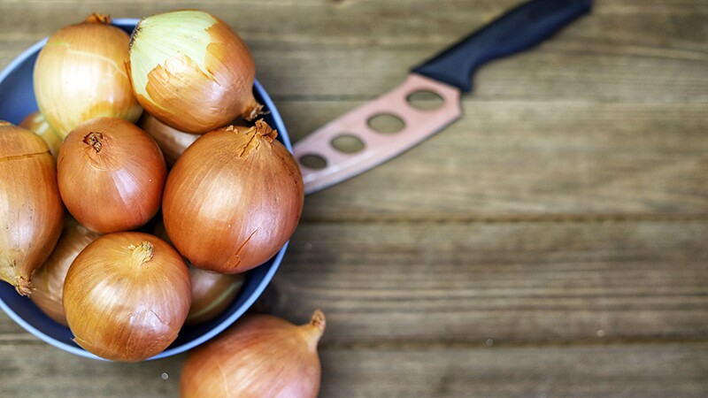 Yellow onions in a blue bowl on a wooden cutting board