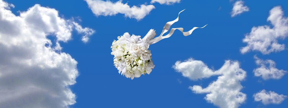 wedding bouquet being thrown through the air with clouds and blue sky behind it
