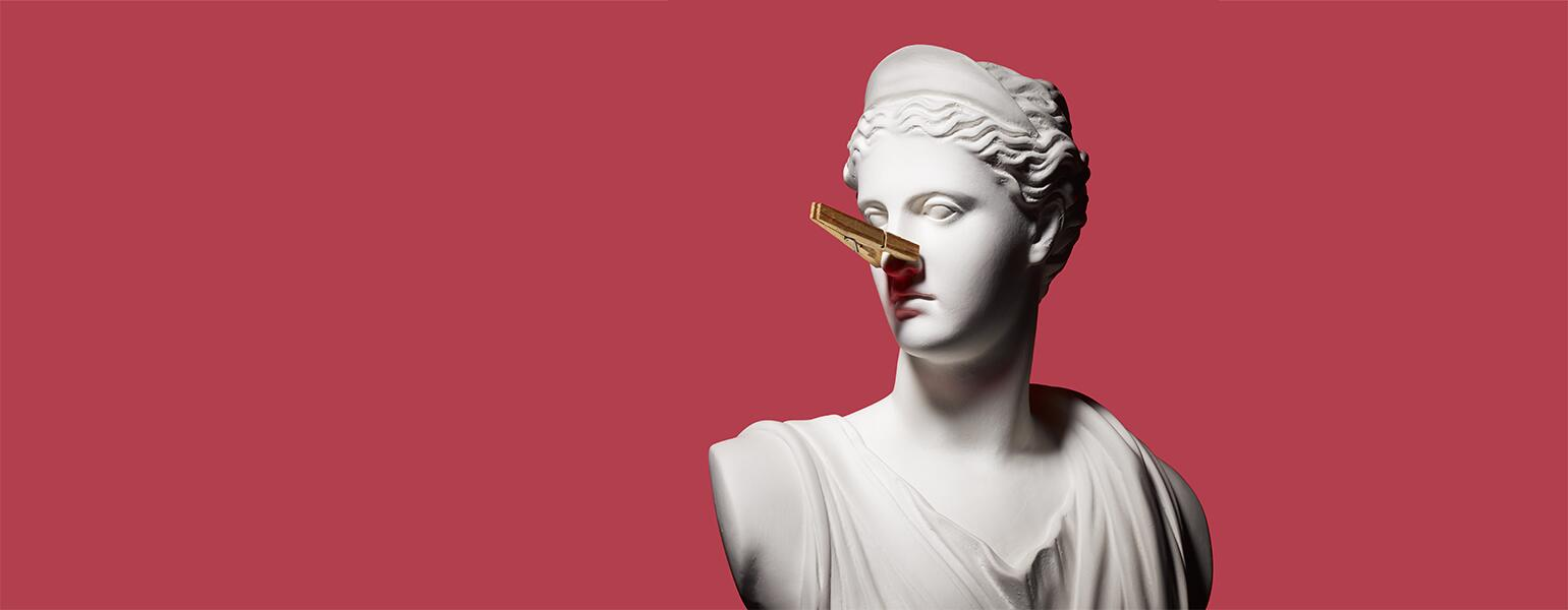 A white bust statue wears a clothespin on its nose to combat the smell of perimenopause symptoms.
