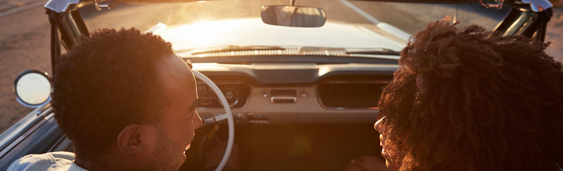 husband and wife in convertible driving into the sunset talking to each other