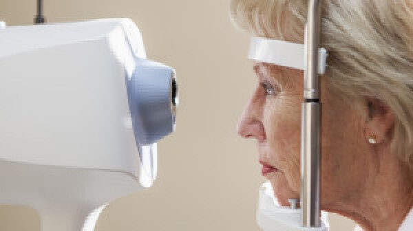 Senior woman (60s) at ophthalmologist's office for eye exam, looking into retina scanner.