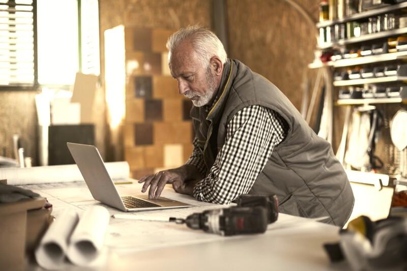 Mature designer looking at laptop