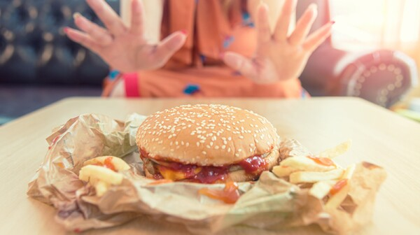 Hands of a woman refusing to eat a burger and fries