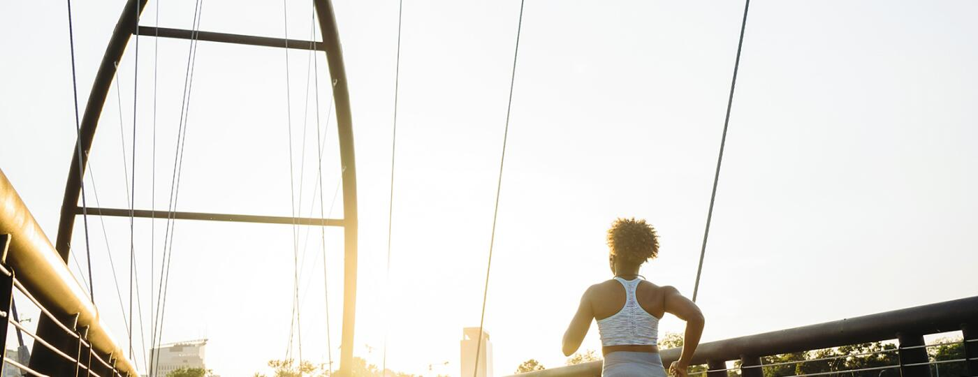 A photo of a woman running down a bridge at sunrise.