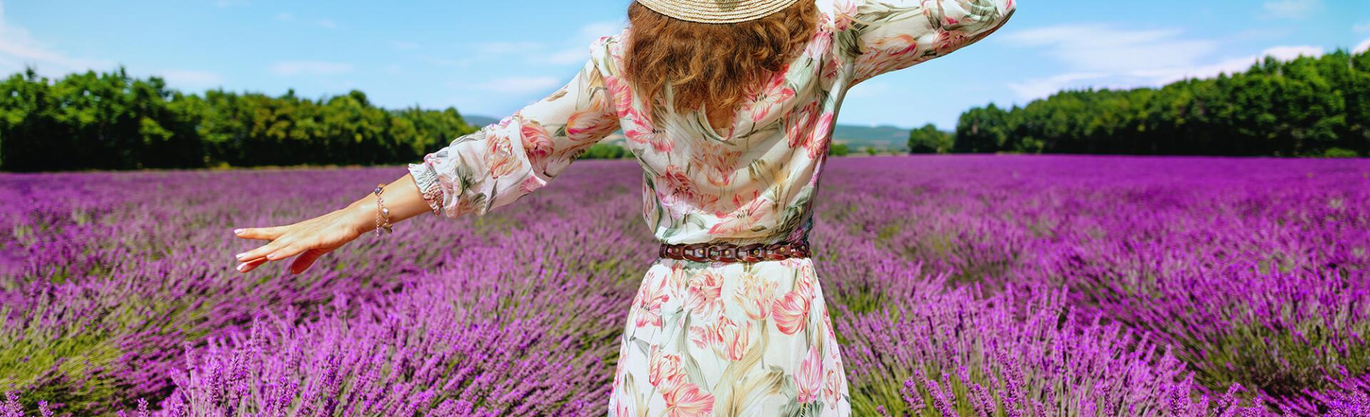 woman in sundress walking through flower field